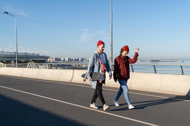 La giovane coppia cammina sul ponte insieme parla di hipster alla moda e si incontra sullo stile di vita giovanile dell'orizzonte urbano