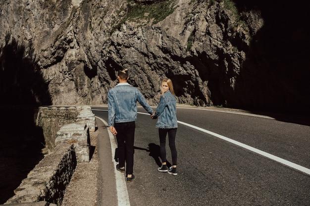 Le giovani coppie camminano sulla strada in montagna.