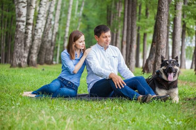 Coppia giovane in una passeggiata con un cane da pastore nella foresta