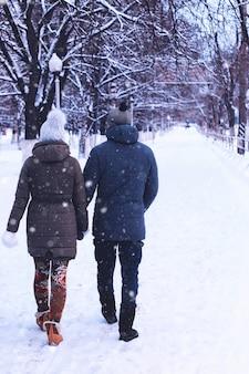 Giovane coppia che cammina lungo la strada d'inverno