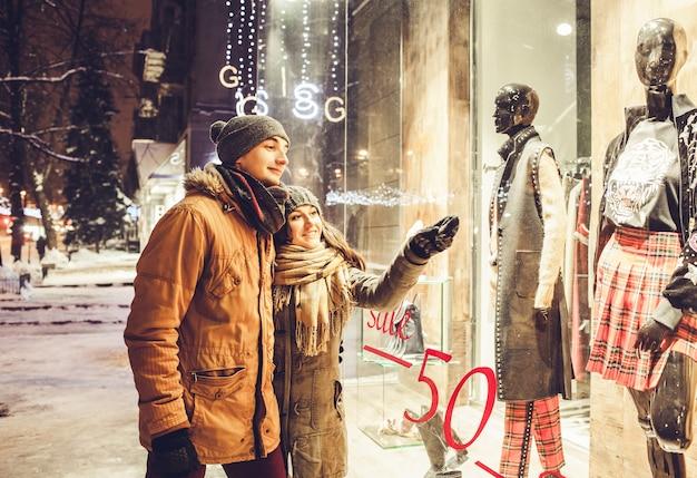 Giovani coppie che camminano nel centro della città e vetrine di notte.