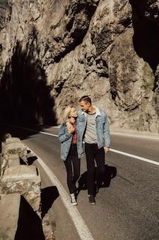 Giovani coppie che camminano sulla strada in montagna con sfondo di rocce