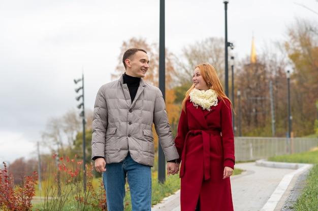 Giovane coppia che cammina e parla nel parco autunnale