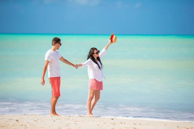 Le giovani coppie che camminano sulla spiaggia tropicale con sabbia bianca e l'oceano del turchese innaffiano all'isola dell'antigua nei caraibi