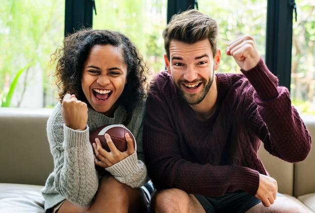 Giovani coppie che guardano football americano a casa