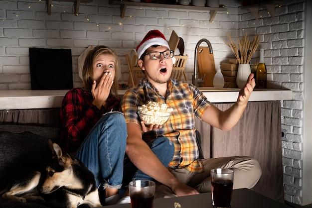 Giovani coppie che guardano film a casa