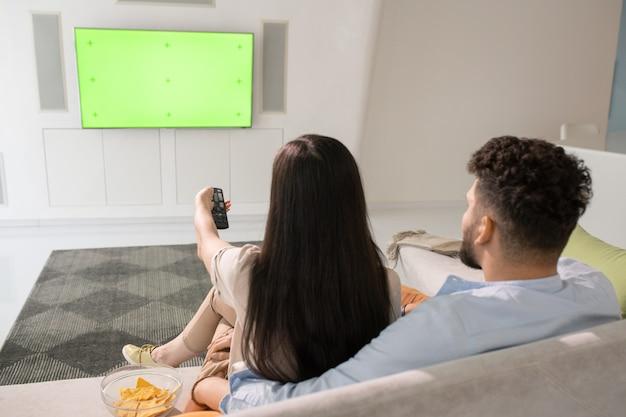 Giovane coppia che guarda la tv mentre si rilassa sul divano in soggiorno