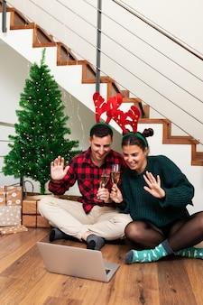 Giovane coppia saluta in videochiamata brindisi con champagne festeggia il natale vertical holiday