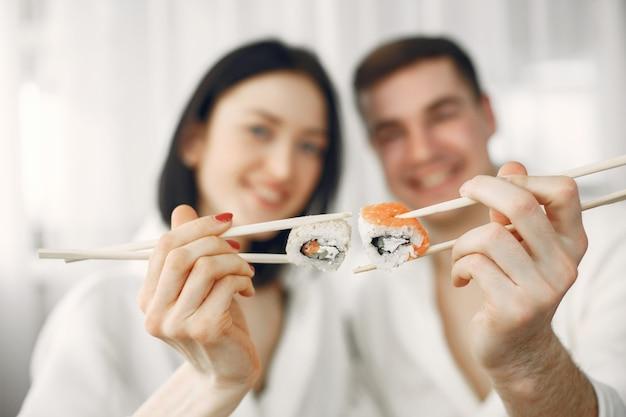 Coppia giovane indossando accappatoi mangiando sushi.