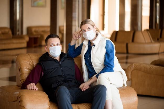 Giovani coppie che indossano una maschera in un salotto dell'aeroporto. concetto di viaggio del virus dell'influenza del coronavirus.