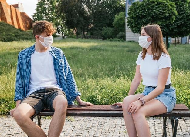 Coppia giovane indossando maschere e parlando con distanza sociale