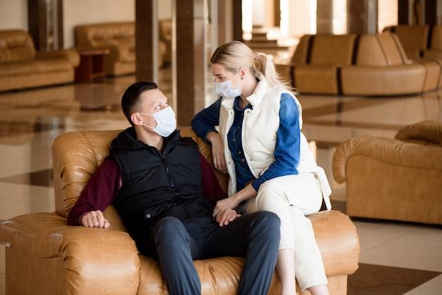 Coppia giovane indossando maschere mediche in una lounge dell'aeroporto