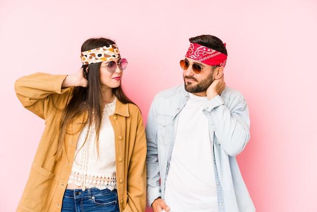 Giovane coppia che indossa un festival di musica vestiti toccando il dorso della testa, pensando e facendo una scelta