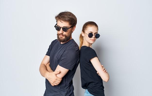 Giovani coppie che indossano occhiali da sole moda abbigliamento casual studio romanticismo sfondo isolato. foto di alta qualità