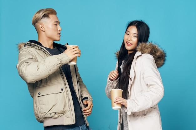 Giovani coppie che indossano abiti invernali e bere caffè