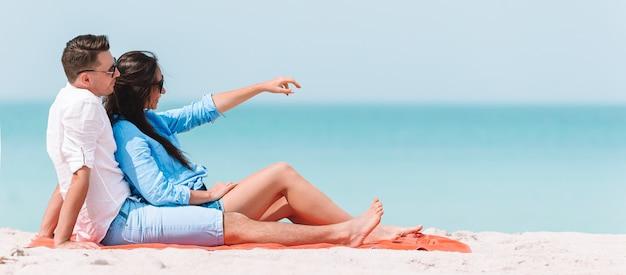 Giovani coppie sulla spiaggia bianca durante le vacanze estive. la famiglia felice si gode la luna di miele