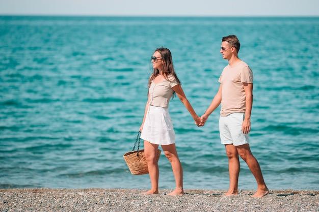 Giovani coppie sulla spiaggia bianca durante le vacanze estive.