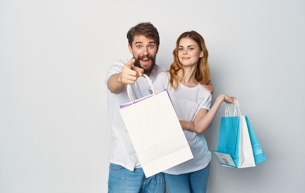 Giovani coppie in magliette bianche con i pacchetti nelle loro mani gioia di acquisto