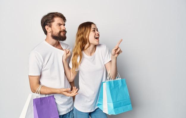 Giovane coppia in magliette bianche con i pacchetti nelle loro mani