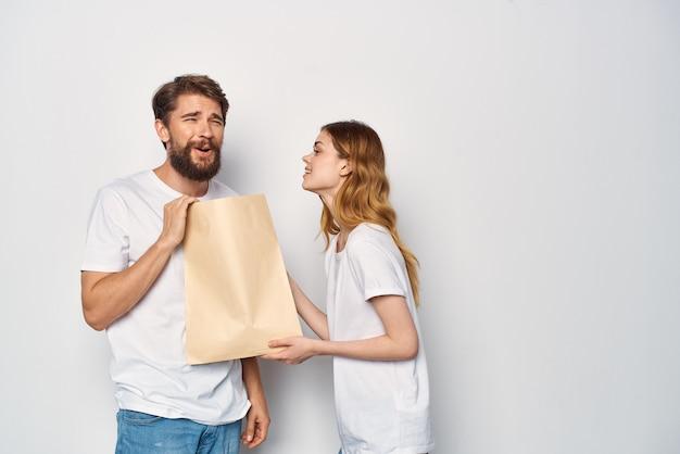 Giovane coppia in magliette bianche sacchetto di carta vendita shopping