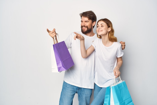 Giovane coppia in magliette bianche con borse in mano per lo shopping divertente