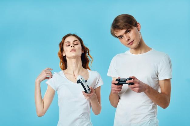 Giovane coppia in magliette bianche con joystick in mano che giocano a intrattenimento