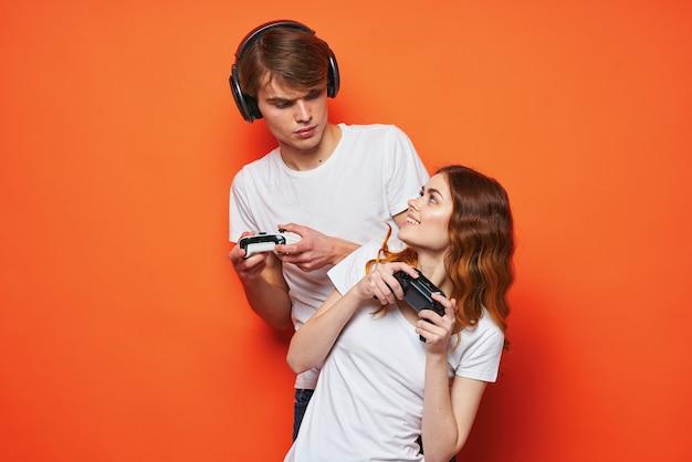 Giovane coppia in magliette bianche con joystick in mano che giocano a gioco amicizia sfondo arancione