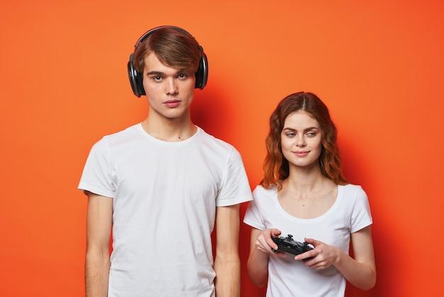Giovane coppia in magliette bianche con joystick che suonano uno sfondo arancione della console