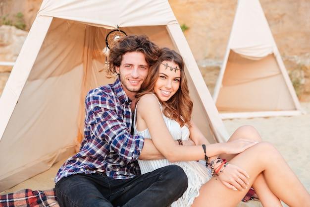 Giovane coppia in wigwam sulla spiaggia