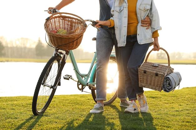Giovane coppia con bicicletta e cestino da picnic vicino al lago in una giornata di sole, primo piano