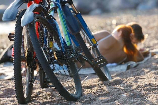 La giovane coppia con le biciclette si rilassa sulla spiaggia. foto di alta qualità