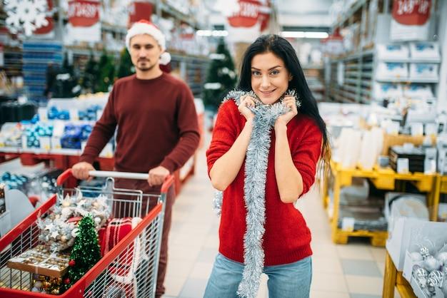 Coppia giovane con carrello nel reparto di decorazioni natalizie nel supermercato, tradizione di famiglia. shopping di dicembre di articoli natalizi o natalizi