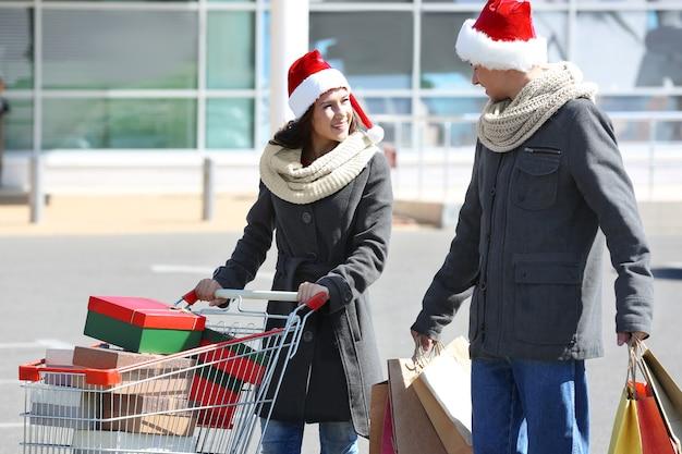 Giovane coppia con acquisti di natale vicino al centro commerciale
