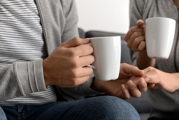 Giovane coppia con tazze di tè che si tengono per mano a casa