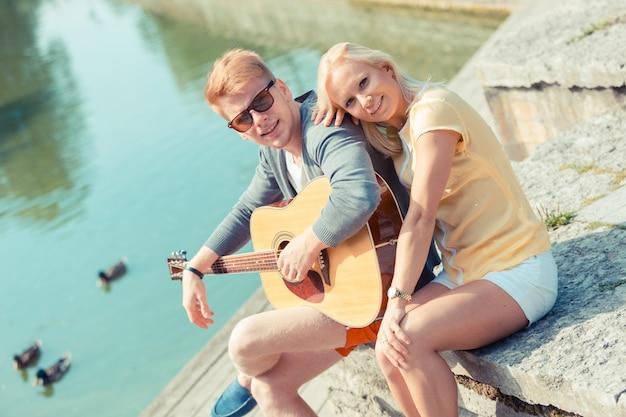 Giovane coppia con chitarra al parco