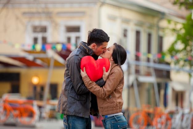 Coppia giovane con giocattolo a forma di cuore baciare per strada in primavera. odessa, ucraina
