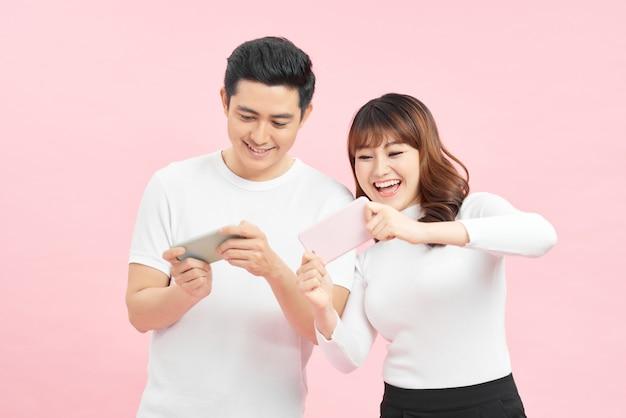 Giovane coppia con telefoni cellulari su sfondo colorato
