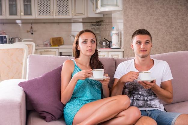 Coppia giovane con tazze di caffè o tè seduti insieme sul divano e guardare la televisione con espressioni vuote