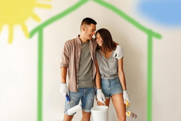 Giovani coppie con i rulli di pittura che abbracciano e che sorridono dopo la verniciatura della parete nella nuova casa
