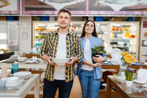 Coppia giovane con piatti in negozio di casalinghi. uomo e donna che acquistano beni per la casa nel mercato, famiglia nel negozio di articoli da cucina