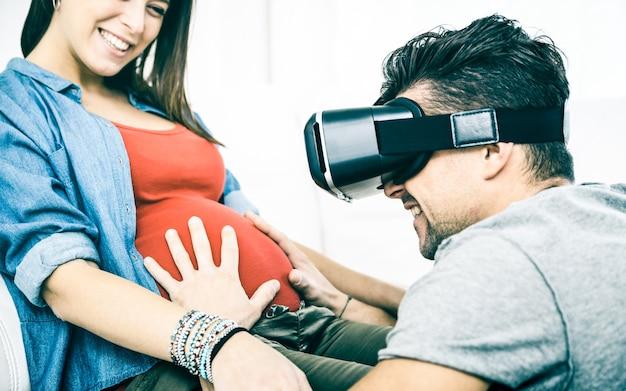 Giovani coppie con la donna incinta che hanno divertimento con le cuffie di tecnologia degli occhiali di protezione di vr