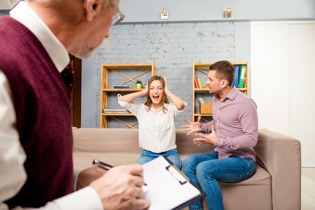 Coppia giovane con problema a litigare alla reception per psicologo familiare