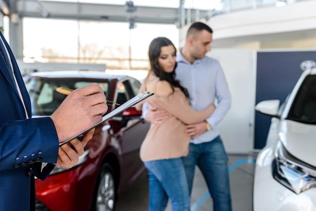 Giovani coppie con il venditore vicino alla nuova automobile che firma il contratto