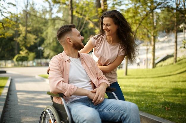Giovane coppia con sedia a rotelle che cammina nel parco