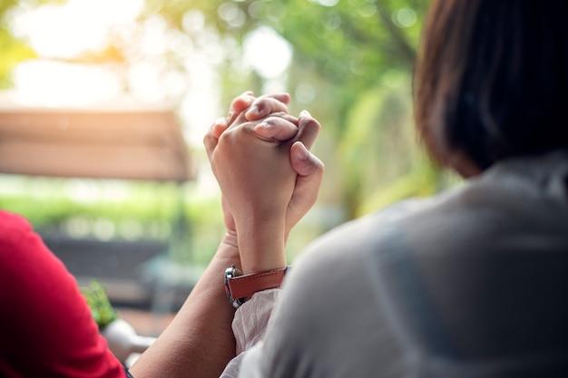 Le giovani coppie si tengono per mano mentre sono seduti insieme a casa, le mani concentrate.