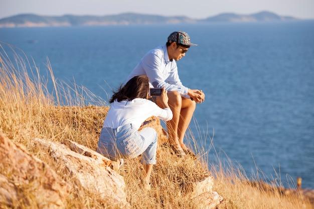 Giovani coppie che si rilassano in alta montagna contro il mare blu