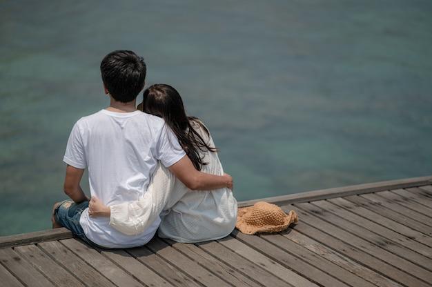 Giovani coppie si siedono e si abbracciano su un ponte sul mare. estate innamorata, concetto di san valentino.