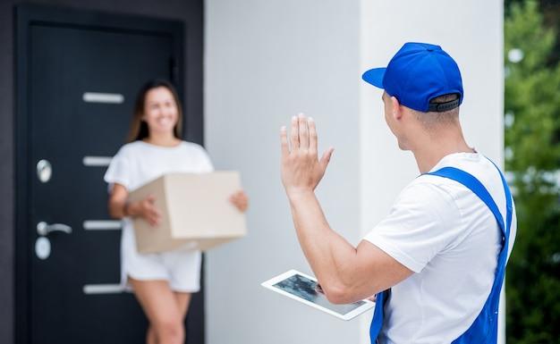 Giovane corriere che consegna merci a una giovane donna a casa.
