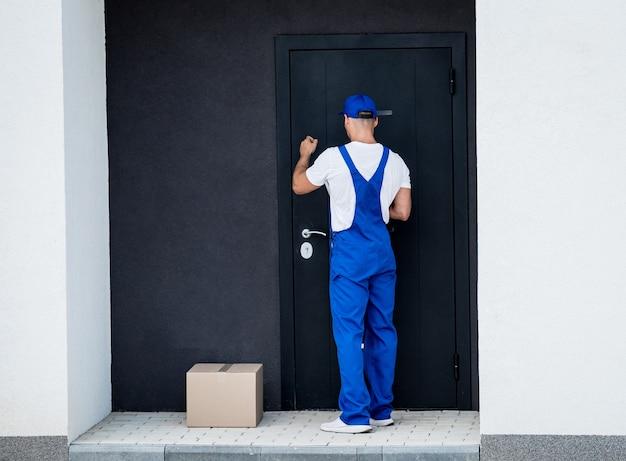 Il giovane corriere consegna la merce alla porta di casa