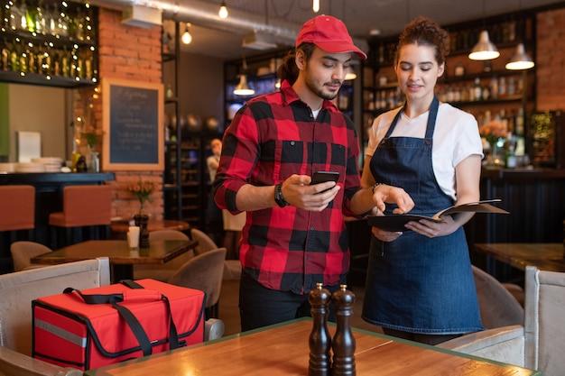 Giovane corriere in flanella che controlla i numeri di telefono e gli indirizzi dei clienti in un apposito libro tenuto dalla cameriera prima di consegnare gli ordini